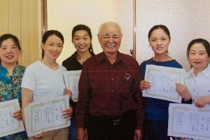 会長と女性スタッフ数名が笑顔で賞状を持って並んでいる写真