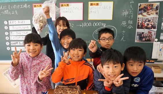 数人の地元小学生と先生が学校の教室で楽しいそうにしいたけと一緒に写っている写真