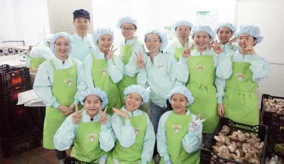 作業着を着たスタッフ十数人が一緒に写っている笑顔の集合写真