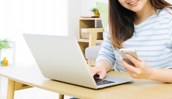 情報を発信するためにパソコンとスマートフォンを操作している女性の写真